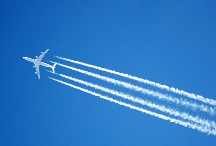 ein blauer Himmel und ein Flugzeug, das Linien im Himmel hinterlässt, ZeroAvia