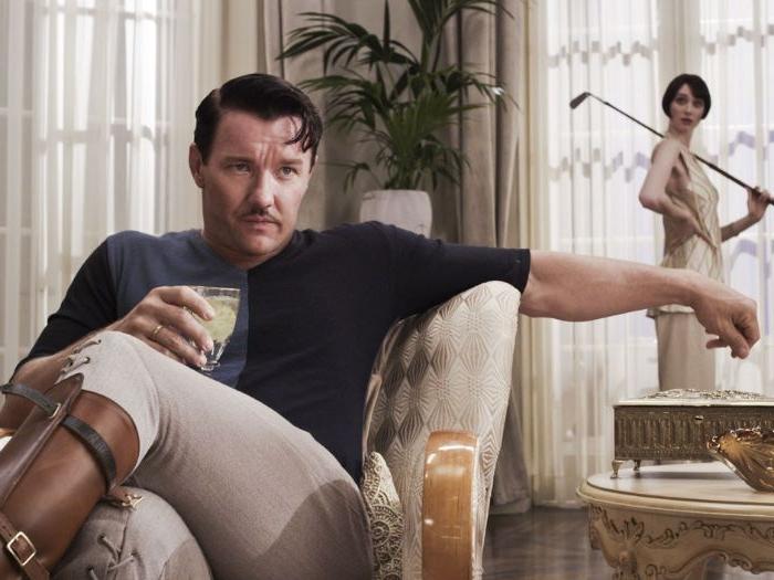 20er jahre, mann mit einen engen hosen, hält ein glas kaffee, seine frau ist hinten