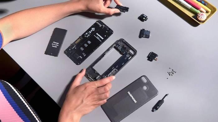 ein kleiner schwarzer schraubenzieher und viele kleine austauschbare module eines smartphones fairphone drei