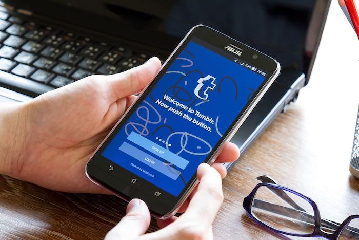 violette brille und hände mit einem schwarzen smartphone mit dem logo von dem sozialen netzwek tumblr