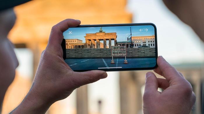 brandenburger tor in berlin und die ehemalige berliner mauer, ein handy mit der neuen app mauAR, die die ehemalige berliner mauer zeigt