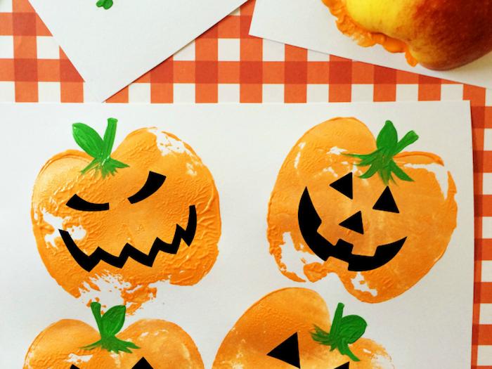 Lustige Halloween Kürbisse malen, Apfel Stempel aufs Papier tupfen, Mund und Augen aus schwarzem Papier schneiden