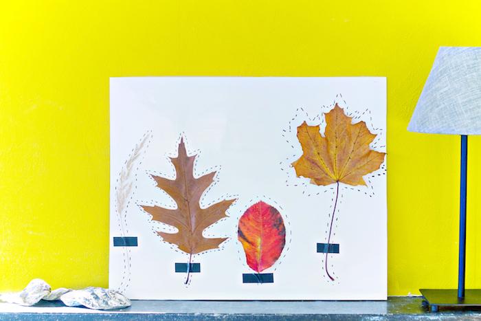 Herbstliche Dekoration mit Kindern basteln, bunte Herbstblätter auf Papier kleben