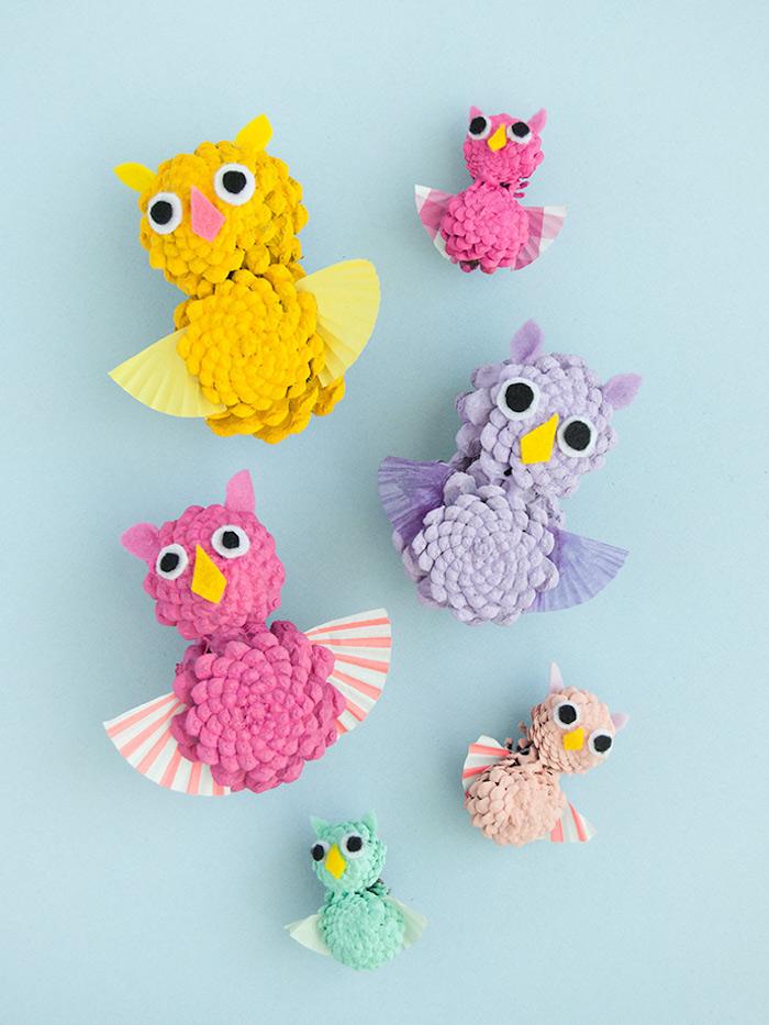 Kleine bunte Uhus aus Zapfen, mit Flügeln aus Papier, mit Augen und Ohren aus Filz