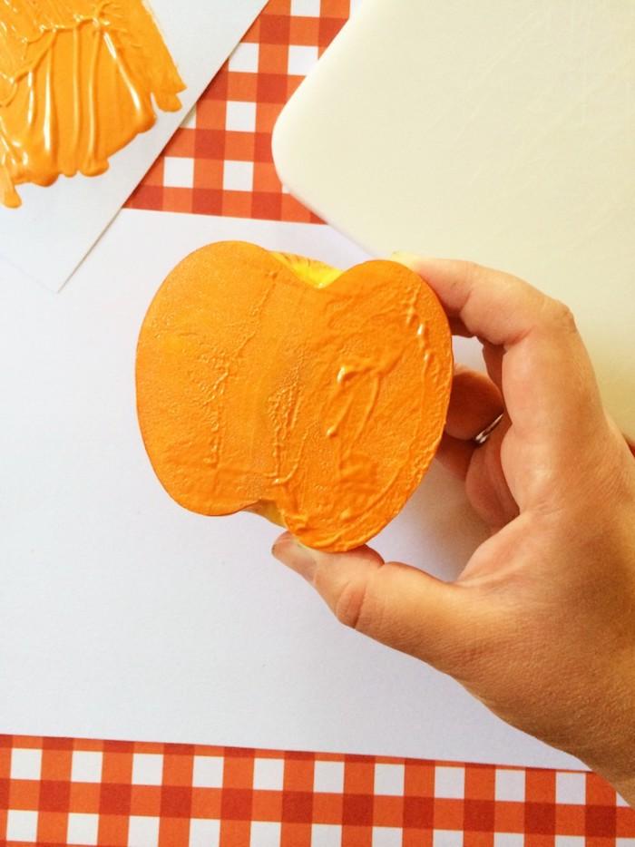 Apfel Stempel selber machen, Apfel halbieren und in Farbe tupfen, Halloween Kürbisse malen