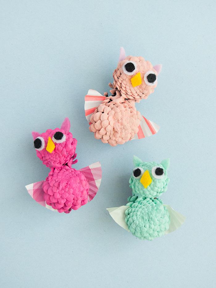 Drei bunte Uhus aus kleinen Zapfen, mit Flügeln aus Papier, Herbstdeko mit Kindern basteln