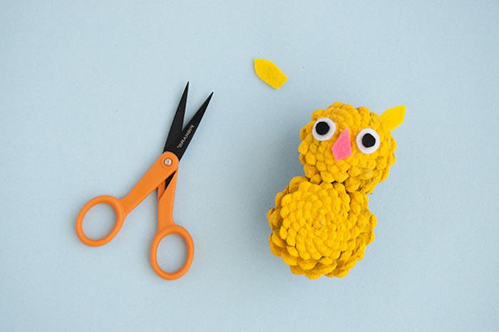 Kleinen Uhu aus zwei Zapfen selber machen, Augen Ohren und Schnabel aus Filz kleben, gelb bemalen