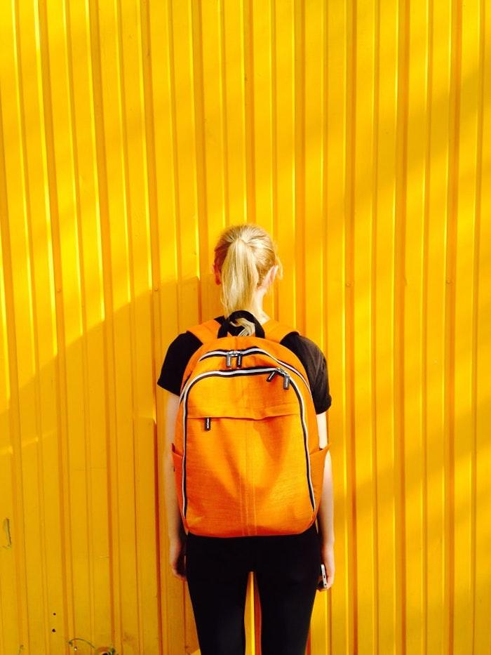 Blondes Mädchen mit gelbem Schulranzen und schwarzem Outfit