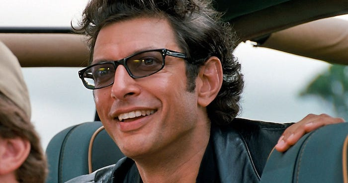 szene aus dem film jurassic park, der schauspieler jeff goldblumm in der rolle von dr ian malcolm, ein mann mit schwarzer brille im auto