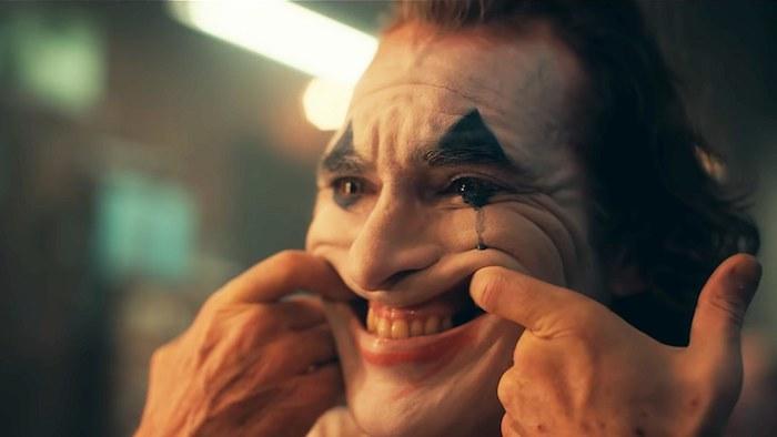 Joker, der schauspieler joaquin phoenix in der rolle des jokers, ein mann mit einer weißen schminke eines clownes