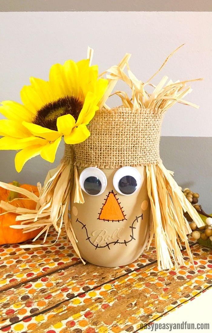 rKreative Herbstdeko selber basteln, Vogelscheuche aus Einmachglas mit Wackelaugen, Stroh für Haare, großer Sonnenblume