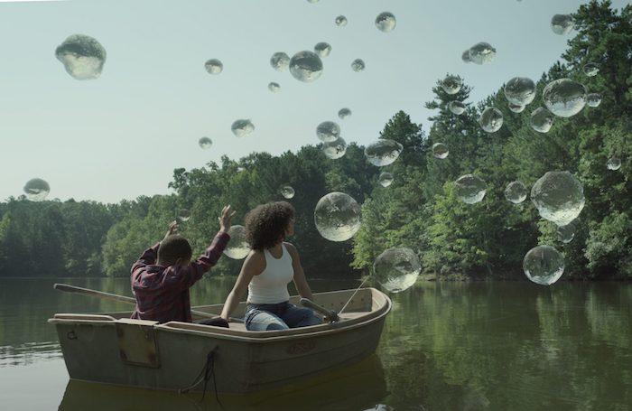 ein kleiner junge mit übernatürlichen kräften, szene aus der netflix serie raising dion, ein boot mit einer frau und einem kind