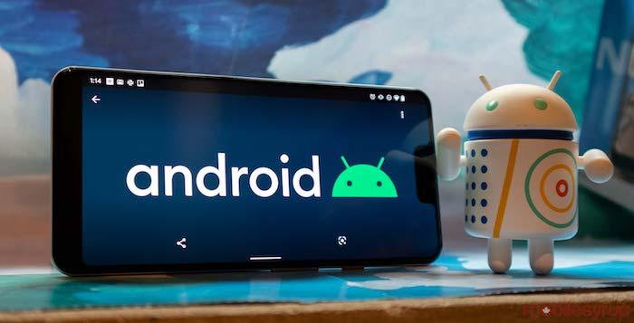 kleiner weißen roboter, ein schwarzes smartphone pixel mit der neuen version des betriebsystem von google android zehn