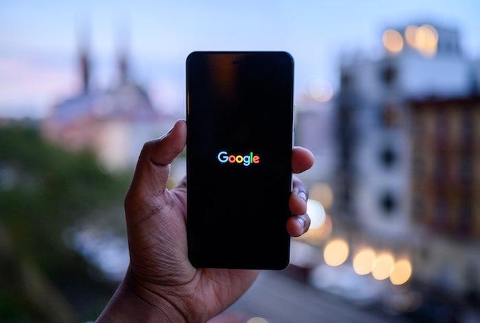 hand eines Manns mit schwarzem kleinen smartphone pixel von google, das betriebssystem android 10