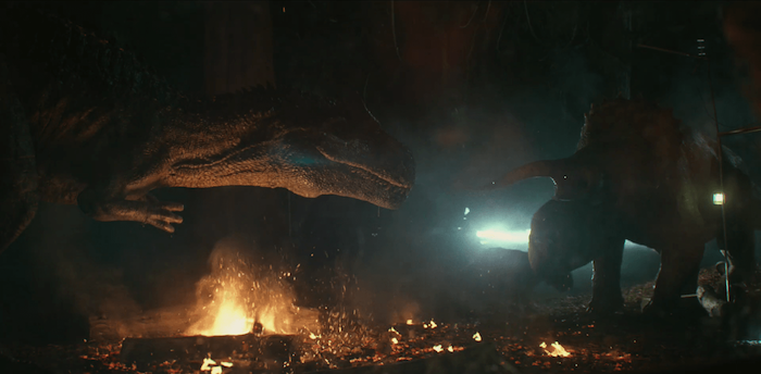 szene aus dem kurzfilm jurassic world battle at big rock von dem regisseur colin trevorrow, wald mit bäumen und feuer, zwei große dinosaurier