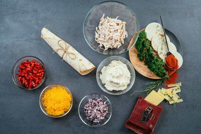 Zutaten für leckere Mini Tacos, rote Paprika, rote Zwiebel und Karotten, Frischkäse und Cheddar Käse, Hühnerfilet und Petersilie zum Garnieren