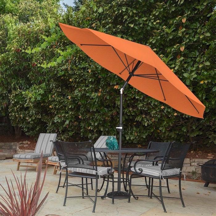 oranger sonnenschirm im garten mit vielen grünen pflanzen, tisch und stühle