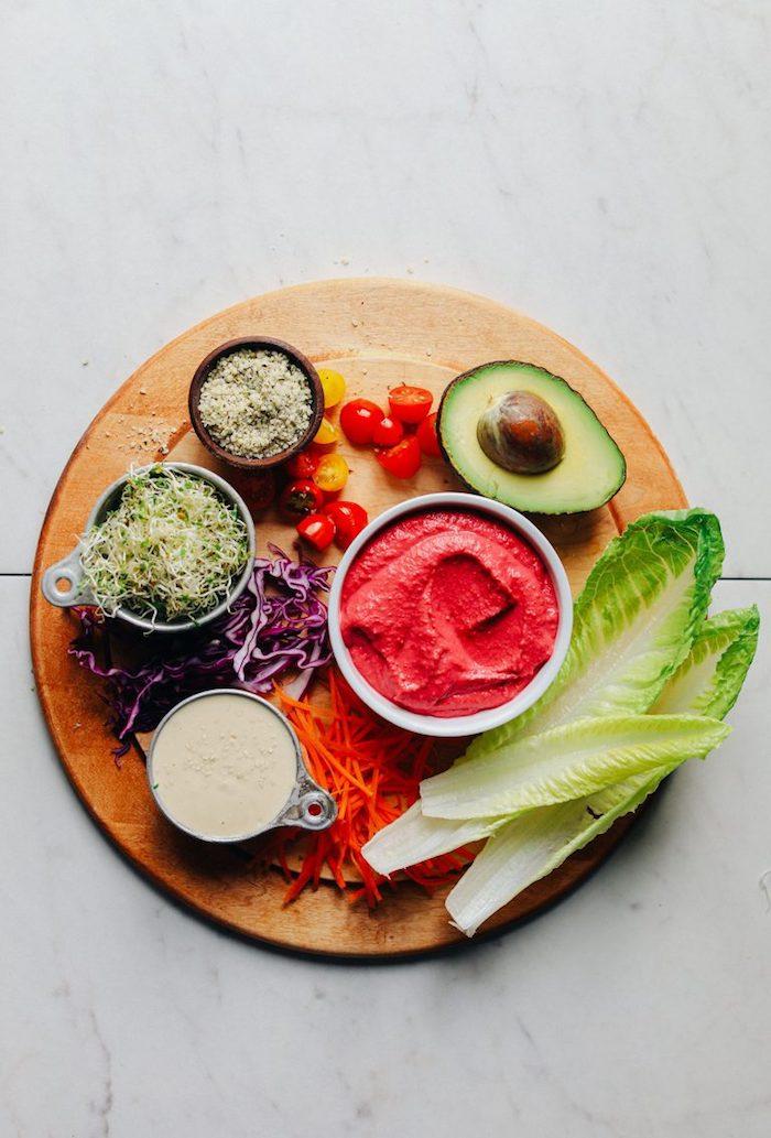 Zutaten für gesunde Tacos, Salatblätter und halbierte Avocado, Cherrytomaten und Rotkohl, Tomatensoße und Sprossen