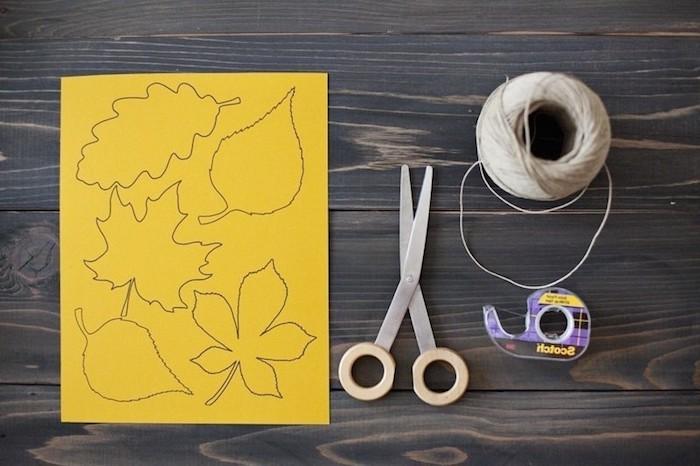 Materialien für DIY herbstliche Girlande, gelbes Papier, Schere und Schnur, Klebeband