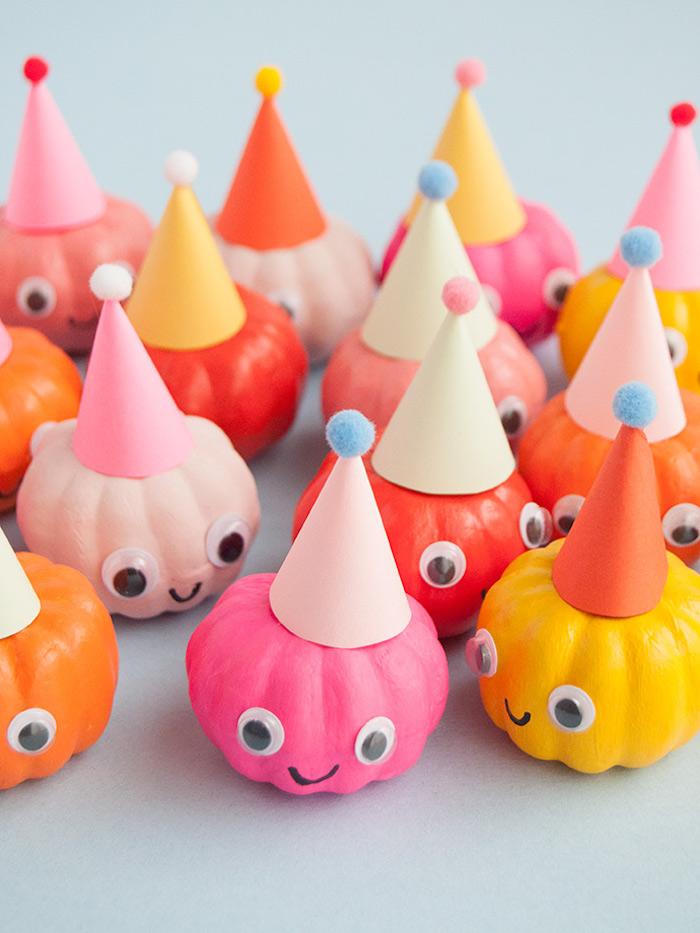 Mini Kürbisse bunt bemalen, mit kleinen Party Hüten und Wackelaugen dekorieren
