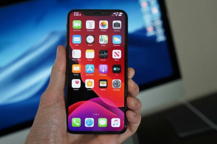 iOS 13 Update, ein Handy mit rotem Hintergrund in der Hand von dem Benutzer