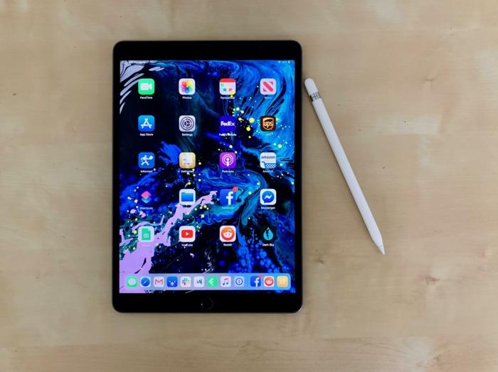 ein iPad mit vielen Apps auf dem Display und ein weißes Apple Pencil