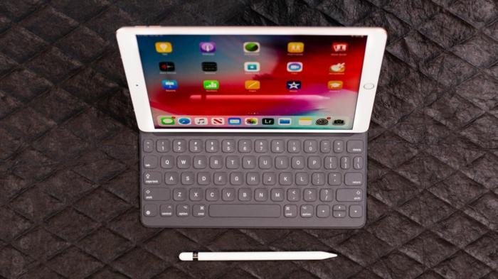 iPad auf einem Tisch mit einem Smart Klaviatur und davor ein Apple Pensil
