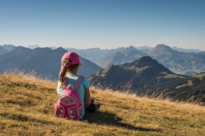 Kleines Mädchen mit blauem T-Shirt und Schmetterling-Schulranzen in Pink