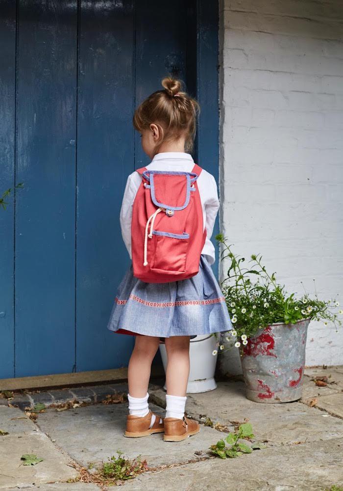 Süßes Mädchen mit rotem Schulranzen, Denim Rock und weißem Hemd
