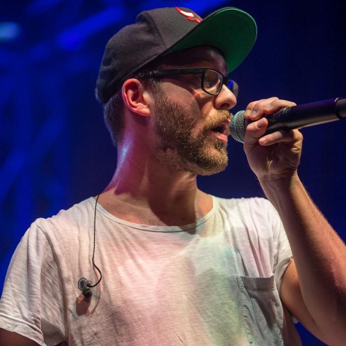 Mark Forster, ein weißes T-Shirt, Brillen mit schwarzem Rahmen, bei einem Konzert