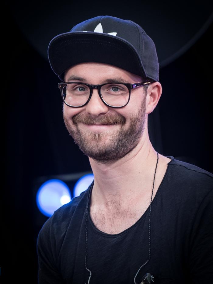 Mark Forster mit einem schwarzen T-Shirt, Brille mit schwarzem Rahmen und Capp