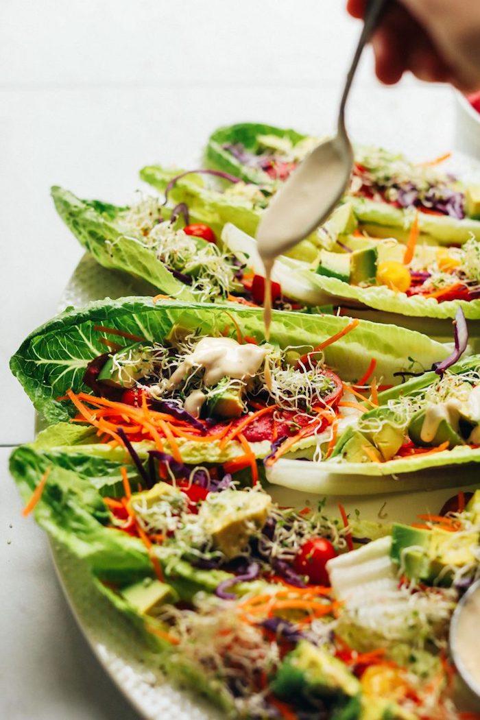 Gesunde Tacos aus Salatblättern mit Sauce garnieren, Ideen für healthy Partyfood