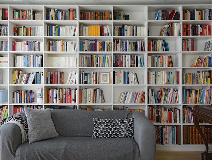 Harmonie bestimmt die Wohntrends von heute, graues Sofa, weiße Regale, viele Bücher