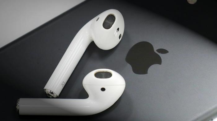 ein graues Smartphone, weiße Kopfhörer, AirPods Pro, ein Logo von Apple