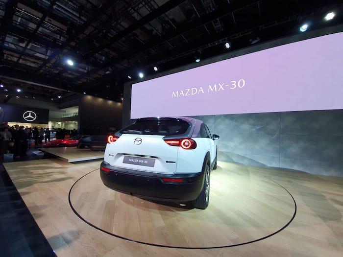 brauner boden aus holz, ein kleiner weißer vrossover, die autoshow in tokyo 2019, das erste weiße elektroauto mazda mx 30