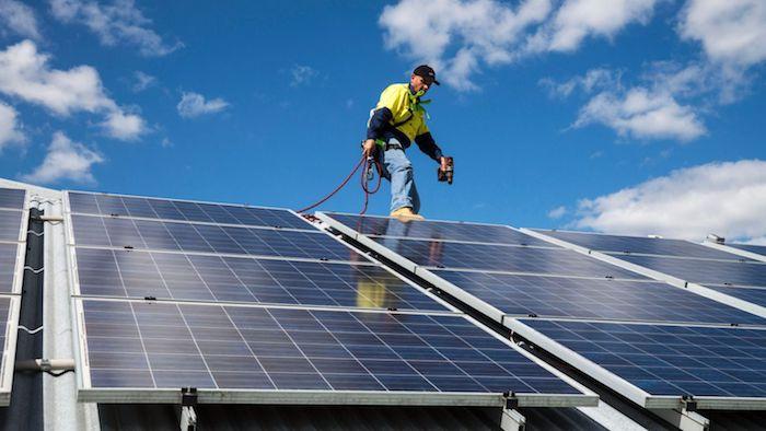 blauer himmel und ein mann, haus mit Photovoltaikanlagen