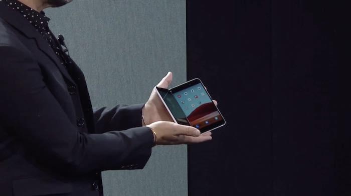 ein kleines smartphone mit zwei klappbaren bildschirmen und ein mann mit einem dunkelblauen anzug, das neue microsoft surface duo