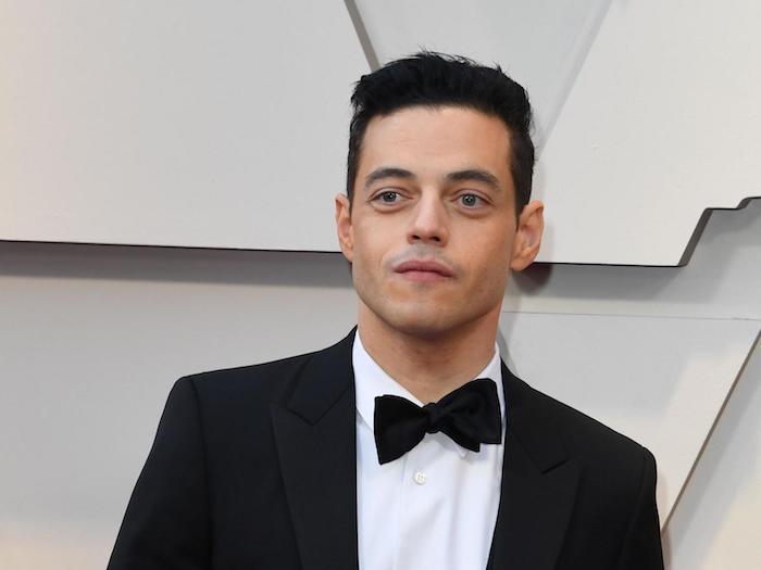 ein junger mann mit weißem hemd und einer schwarzen fliege ind schwarzem sako, der schauspieler rami malek