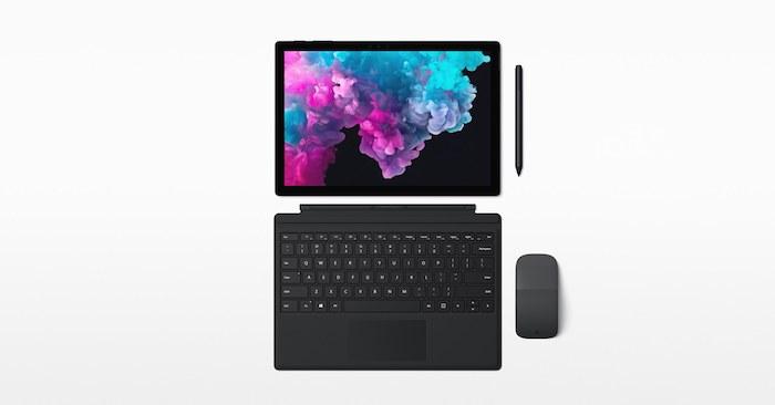 eine graue maus und ein laptop mit einem bunten bildschirm und schwarzer tastatur, das neue surface pro x