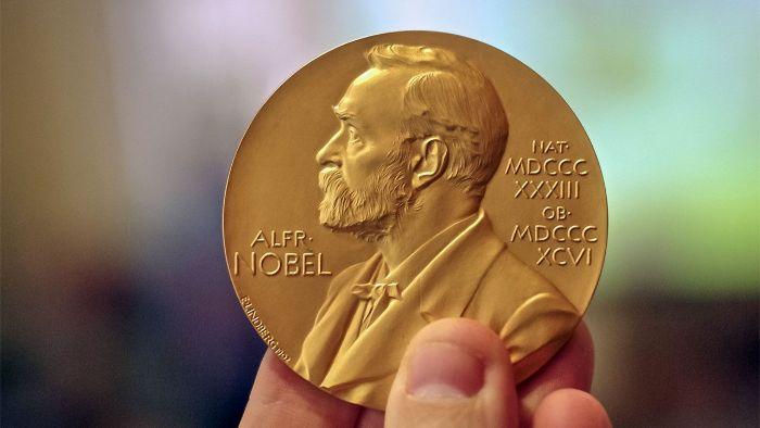eine goldene münze mit alfred nobel, eine hand und der literaturnobelpreis, ein mann mit goldenem bart