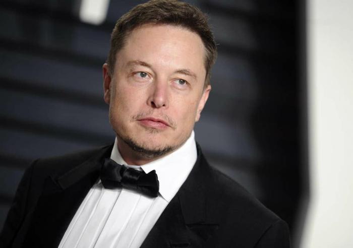 Elon Musk ist zufrieden, weil die Tesla Aktien steigen, hier ist er mit schwarzem Anzug