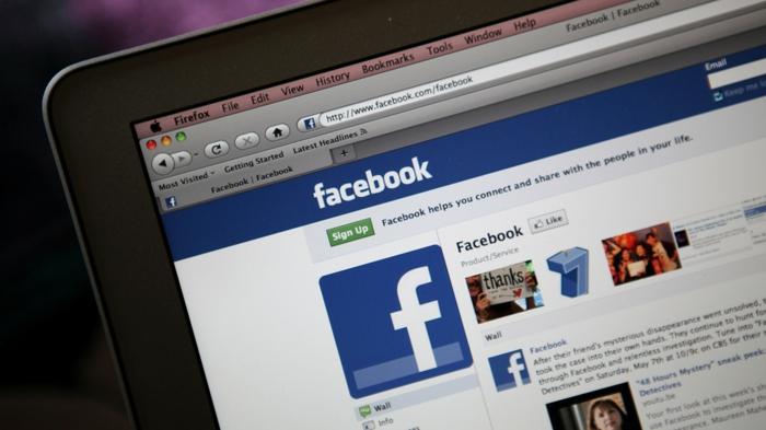 eine Ecke von Laptop mit dem Logo von Facebook, die neue Funktion Facebook News