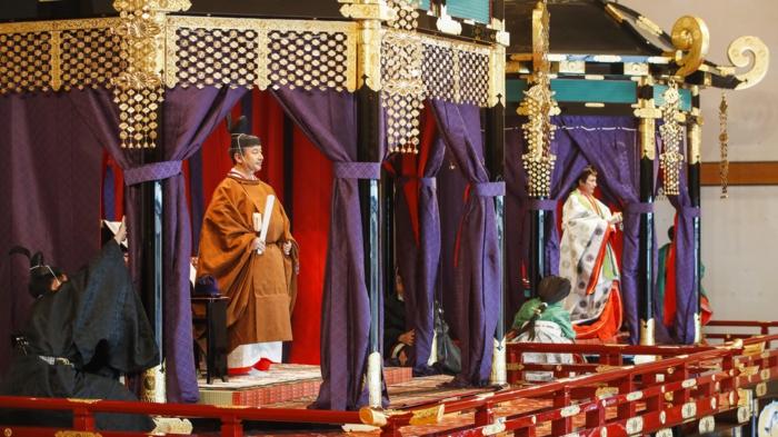 der Kaiser Naruhito und die Kaiserin Masako setzen sich auf ihre Thronen