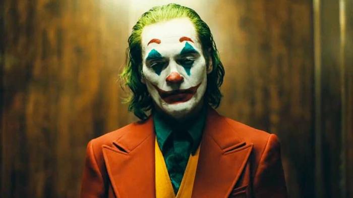 der Joker scheint zu schlaffen, ein roter Anzug und grünes Hemd, weiße Schminke