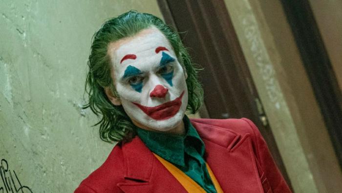Joker, weißes Gesicht, roter Mantel, grünes Hemd, ein Serienmörder wie Clown