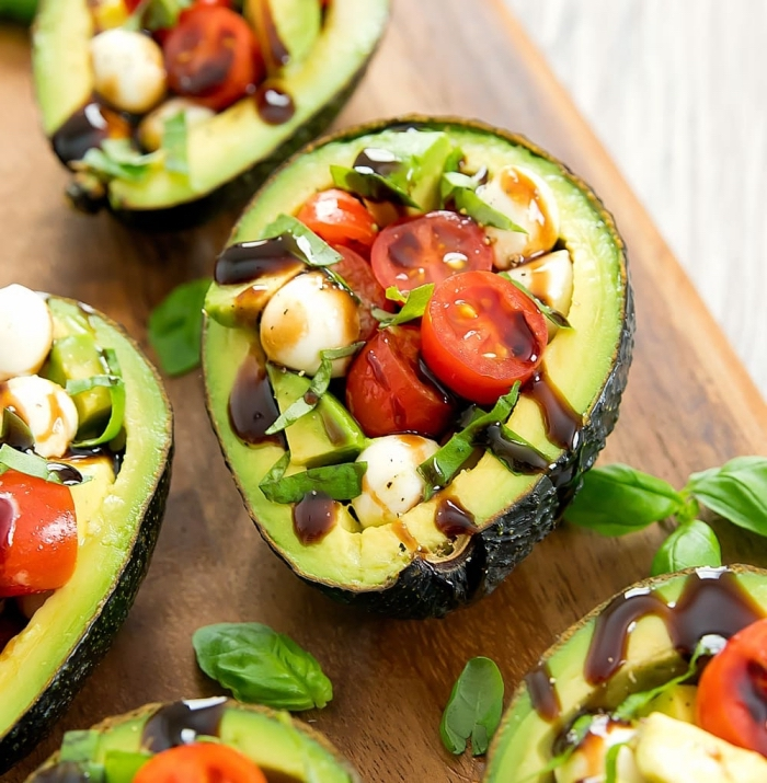 ketogene ernährung, gesundes frühstück ideen, avocados mit füllung aus cherry toamten und mozzarella