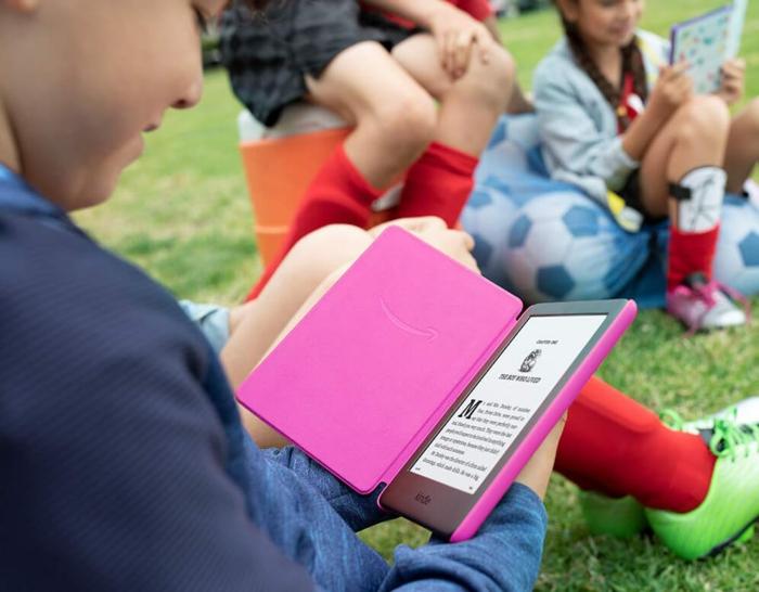 rosa Hülle, zum Lesen in den Freien, Kindle für Kinder auf einem Rasen