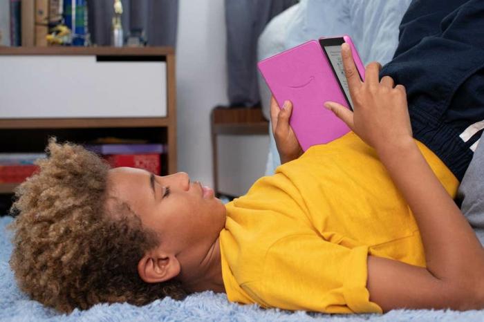 ein Junge mit einem Kindle, Kindle für Kinder in rosa Hülle, das Kind liegt und liest