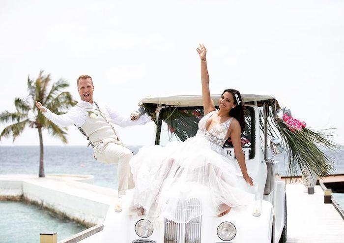 ein mann und eine braut mit weißem blrautkleid, ein weißes auto, meer und palmen, der komiker Oliver Pocher und amira aly als brautpaar