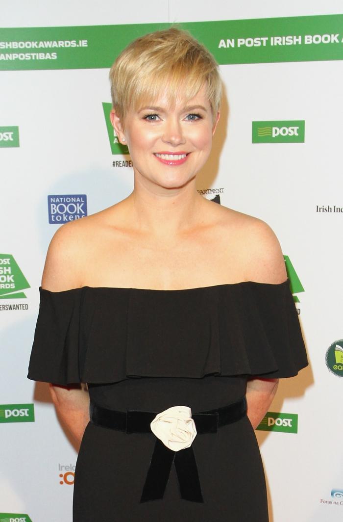 Cecelia Ahern ist mit einem schwarzen Kleid angezogen, mit einer weißen Rose am Gürtel